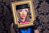 pic of cabaret  - beautiful cabaret woman posing with golden frame against retro wallpapers - JPG