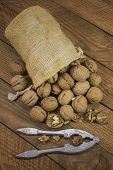 image of nutcracker  - Nuts in the pouch of burlap and Nutcrackers on wooden boards
