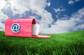 stock photo of postbox  - Red email postbox against green field under blue sky - JPG