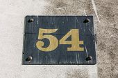picture of plaque  - A plaque displaying the number 54 on a wall - JPG