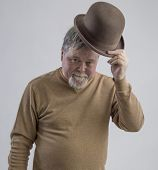 stock photo of older men  - Older man in brown sweater wearing brown derby and smiling - JPG