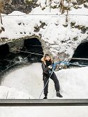 stock photo of cave woman  - The girl in the mountaineering gear coming down on a rope to the cave in winter - JPG