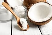image of exotic_food  - Coconut with jars of coconut oil and cosmetic cream on wooden background - JPG