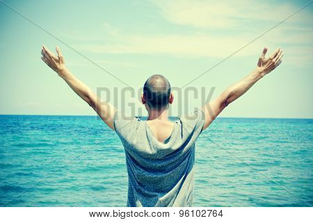 closeup of a young caucasian man seen from behind with his arms in the air in front of the ocean, feeling free, with a slight vignette added