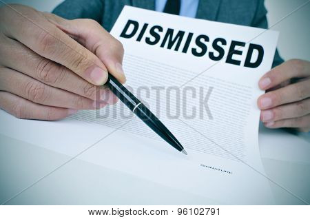 a young businessman sitting at his office desk shows a document with the word dismissed written in it and points with a pen where to sign