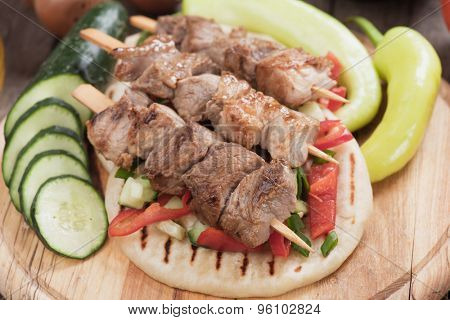 Souvlaki or kebab with vegetable salad on pita bread