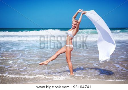 Beautiful woman dancing on the beach wearing stylish swimsuit and holding white scarf, relaxation outdoors on tropical resort, enjoying freedom and summer vacation