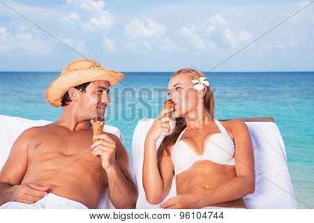 Happy couple relaxing on the beach resort, sitting on sunbed, eating tasty ice cream and looking on each other, romantic honeymoon