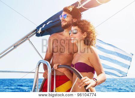 Joyful couple driving sailboat, enjoying water summer adventure, spending honeymoon in the sea cruise, romantic relationship, happy young family