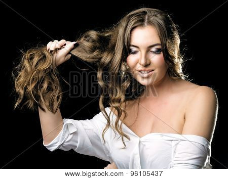 beautiful young woman, showing her long curly hair,  against dark studio background