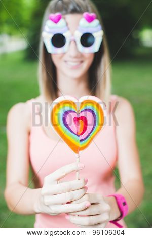 Teenage girl hiding behind lollipop