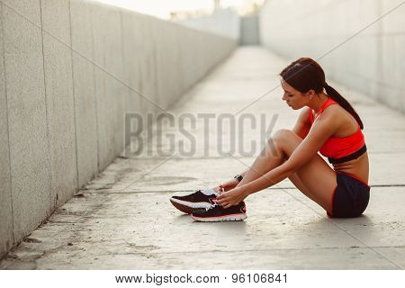 runner woman sitting on the ground and tie laces