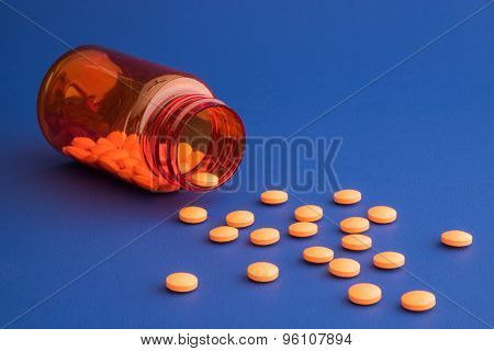 Orange pills spilling out of orange bottle