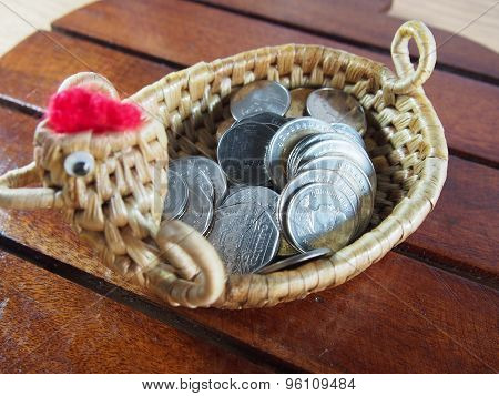 Coins, Money In The Basket, Handmade Chicken Shape, Weaved From Water Hyacinth On Wood Background