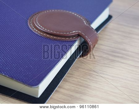 Purple Business Notebook With Brown Skin For Closing On Wood Background