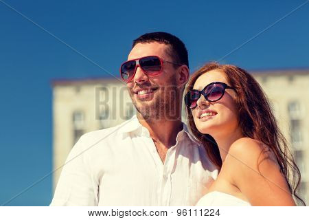 love, travel, tourism, people and friendship concept - smiling couple wearing sunglasses hugging in city
