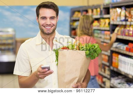 Portrait of smiling handsome man buying food products and using his smartphone at supermarket