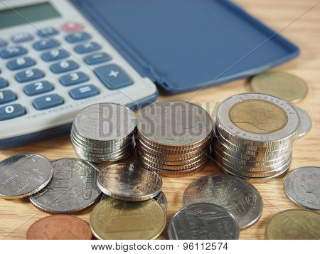 Pile Of Coins, Baht Money And Calculator On Wood Background