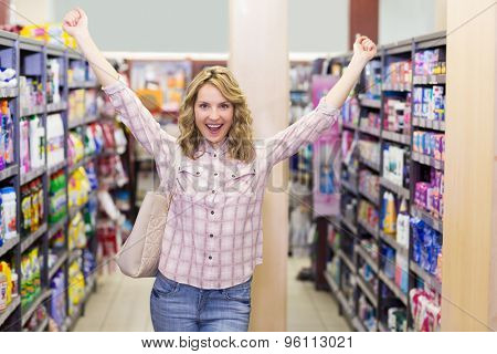 Portrait of a happy smiling blonde woman in supermarket