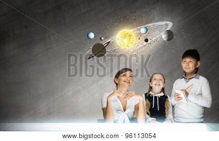 Cute boy of school age and teacher exploring space system