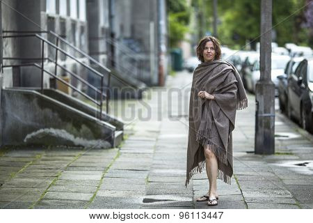 Young attractive woman in a poncho standing in the street near the house.