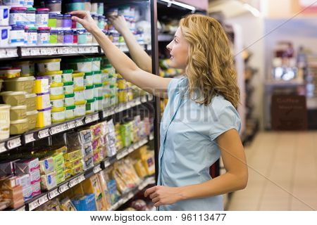 Pretty blonde woman taking a products in shelves in supermarket