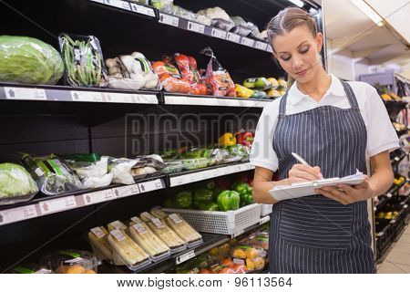 Pretty blonde woman taking note in aisle in supermarket