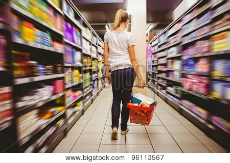 Photo of a woman walking with his trolley on aisle at the supermarket on selective focus