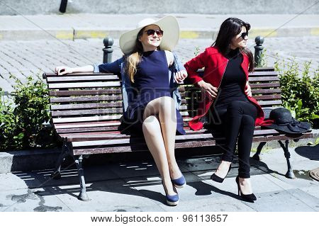 Two Young Women On A Bench Sunbathing