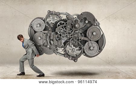 Young businessman carrying huge gears mechanism on back