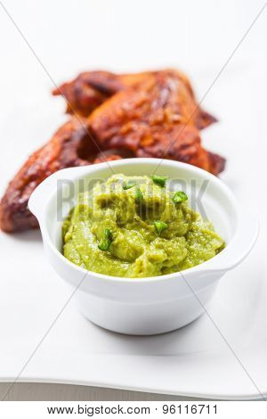 Grilled chicken wings with guacamole on white plate