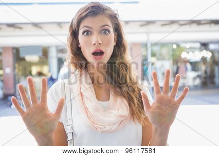 Portrait of astonished woman touching window with both hands at the shopping mall