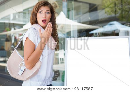 Portrait of surprised woman standing next to a blank board at the shopping mall