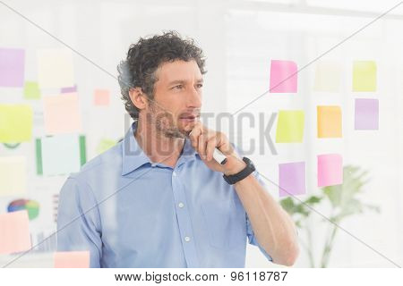Puzzled businessman looking at note on the wall in the office