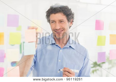Puzzled businessman looking at notes on the wall in the office