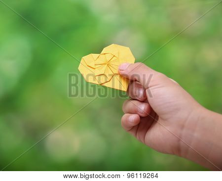 close-up little boy holding paper heart