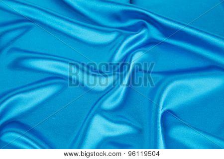 Soft folds of light blue silk cloth.