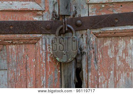 Old padlock on a wooden door.