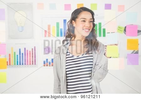 Pretty designer looking  at notes  on window in the office
