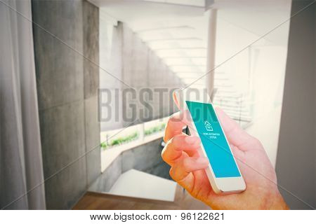 hand holding smartphone against stylish modern home interior with staircase