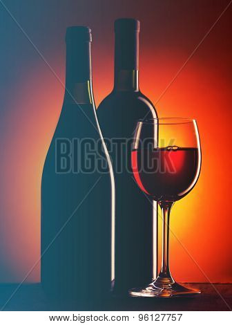 Bottle and glass of red wine on dark red background.Filtered image: cool cross processed vintage effect.