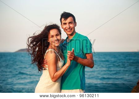 Girl And Guy Hugging Against Azure Sea