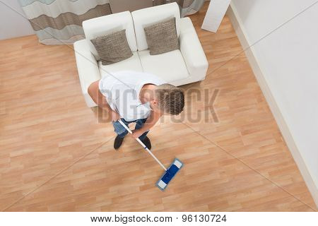 Young Man Mopping Floor