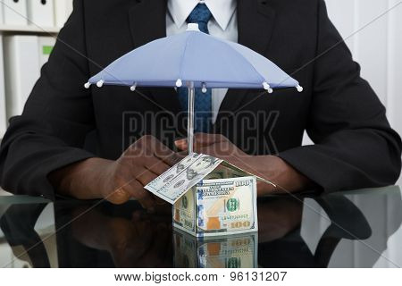 Businessman Protecting House With Umbrella