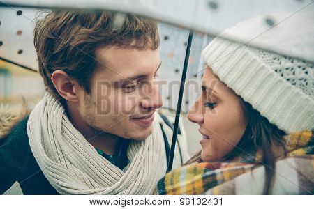 Young couple looking at each other under umbrella outdoors