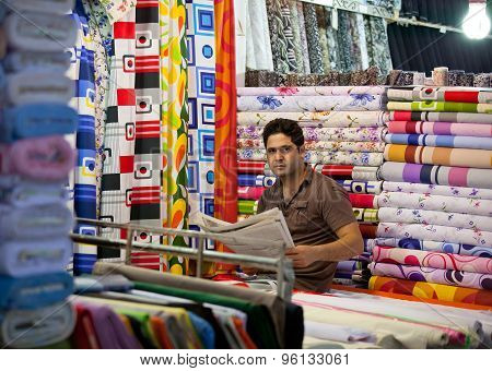 Young Man Selling Fabrics In Traditional Bazaar Of Tehran