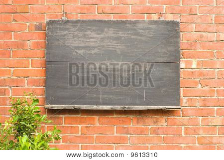 Aged Blackboard On Red Brick Wall.