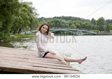 Young beautiful blonde woman in a white tunic sits on a wooden pier on the lake