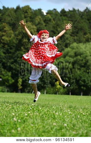 Little girl in a red sundress jumping for joy on a green field