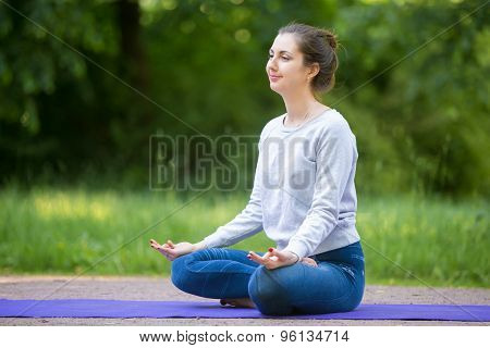 Smiling Young Woman Meditating In Park